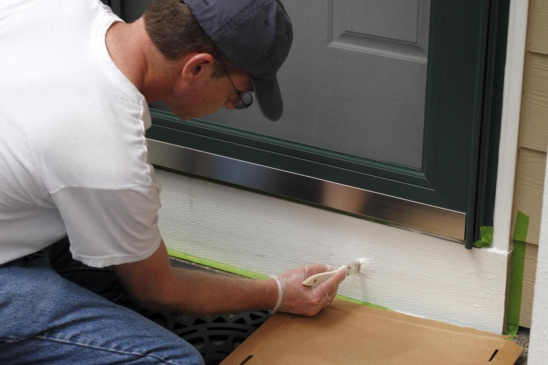 man painting a door